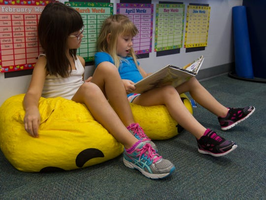 """Kadence Newman, right, and Emily Pietrusiewicz, both 7, sit on bean-bag chairs while reading the book """"To Market, To Market,"""" Wednesday morning (8/17/16) at Gulf Elementary School in Cape Coral as part of Jennifer Jendrusiak's 2nd grade class. The classroom is one of a handful that uses alternative seating options and flexible activities in order to encourage the students' decision making process."""