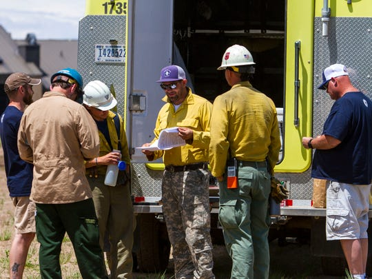Fire crews go over information on the Brian Head fire at the Navajo Lodge parking lot in Brian Head on Tuesday, June 20, 2017.
