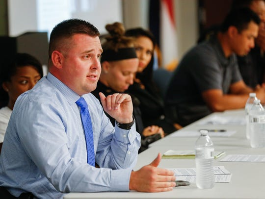 Detective Cpl. Justin Thorn, left, answers a question