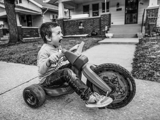 Jason Wehr, 5, makes revving engine sounds as he cruises down the street in Indy's Near Westside on his Teenage Mutant Ninja Turtles Big Wheels bike on a warm day on Monday, Feb. 20, 2017.