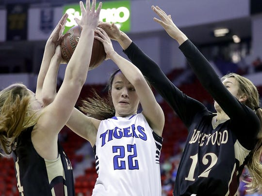 Wrightstown forward Kailee Van Zeeland fights through a trap against Edgewood players Estella Moschkau and Brita Hovde in the WIAA Division 3 girls state basketball semifinal Thursday at the Resch Center.