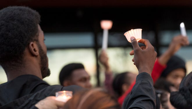 Josiah Washington holds up a candle with other family and friends of Jontell Reedom on Tuesday, March 13, 2018 along Cross Avenue near the place where Reedom had an altercation with Tulare Police on Monday. Reedom, a standout athlete at Tulare Union in 2008, died from gunshots he received during the struggle.