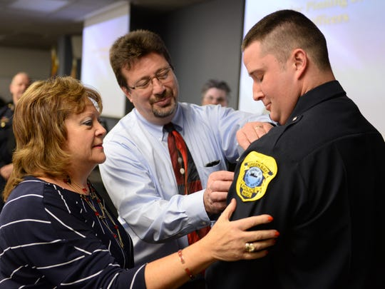 The Green Bay Police Department swore in five new officers April 6, 2015. Ptl. Mackenzie Teske has his shield pinned to his uniform by his parents Nina and John Teske Megan following the oath.
