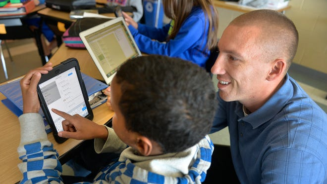 Teacher Garrick Grace works with sixth-grader Zakaria Ibrahim to show him the proper way to create folders in his iPad for his C4 (Community, College, Career, Citizenship) class on Tuesday, Oct. 13 at South Junior High School.