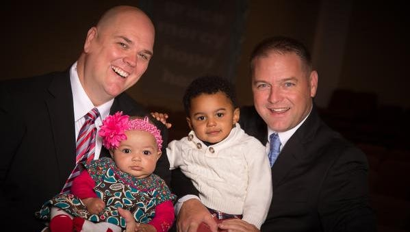 Brian Copeland holds daughter Esther as husband Greg Bullard holds son Micah.
