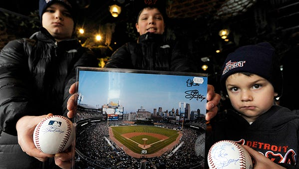 Brothers Austin, 10, Alex, 12, and Aiden Zielke, 4, all of Chesterfield Township, show the autographs they scored Saturday at TigerFest.