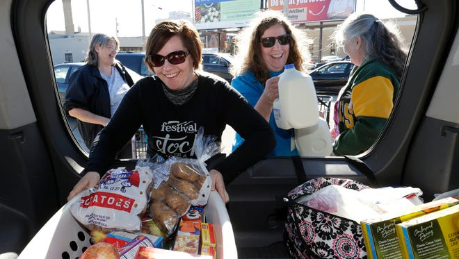 Jennifer Maertz and Linda Hansen, a Community Foundation employee, load food items for Judy Dombrowski, far left, and Kim Dewindt, far right, both of Shiocton, during the annual Stock The Shelves campaign kick-off event Nov. 13 in Appleton. Feeding America Eastern Wisconsin brought a semi-truck full of food items for a mobile food pantry.