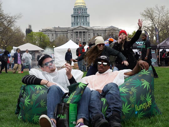 Kevin Barron and La-Sean Moore, both marijuana tourists from North Carolina, share a joint at Denver's Civic Center Park during the annual 420 rally while sitting on an inflatable cannabis-decorated couch.