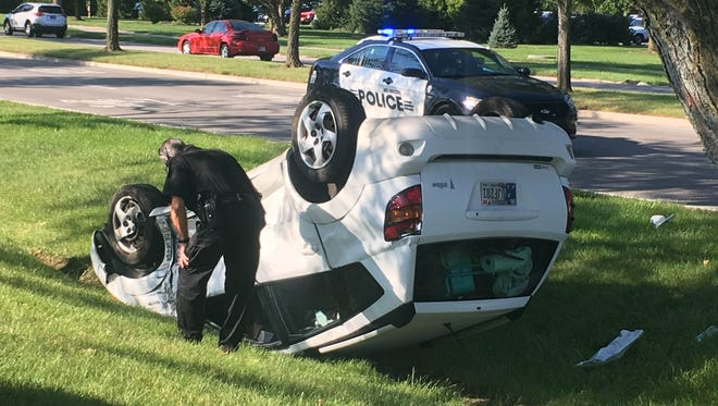 Muncie police investigate a car that rolled over in front of the Ball State University football stadium Tuesday morning. The driver, a 20-year-old student, was taken to the hospital by ambulance, police said.