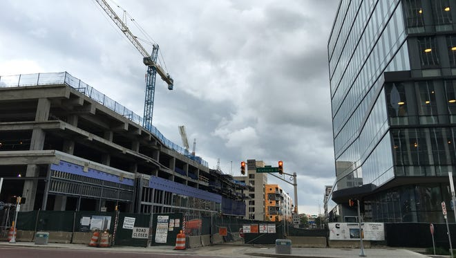 The 360 Market Square apartment tower (left) won't be completed until at least November 2017. Cummins' new distribution headquarters (right) broke ground about the same time as 360 Market Square, yet will be completed in December.