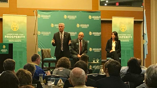 Marty Jackley, left, answers a question Tuesday evening in a candidate forum in Sioux Falls. Americans for Prosperity State Director Don Haggar, center, and Kristi Noem, right, listen.