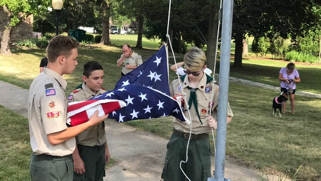 Troop 45 Boy Scouts Jake Dunn (from left) Dominic Ciaramitaro and Robert Ruff raise the flag outside CARES of Farmington Hlls. As his Eagle Scout project, Dunn organized a rebuild of the flag pole area.