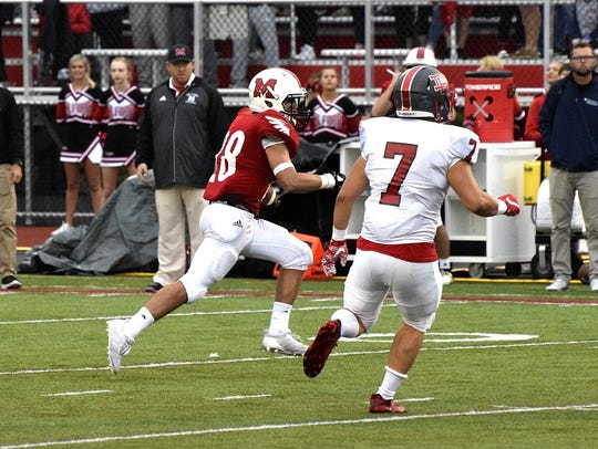 Milford's Cameron Kells (28) rounds the corner and