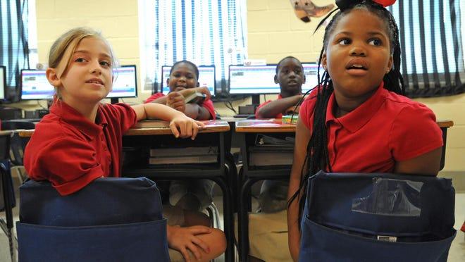 Westwood Elementary students Aliya Henderson (left) and Savannah Green listen to their teacher Wednesday.
