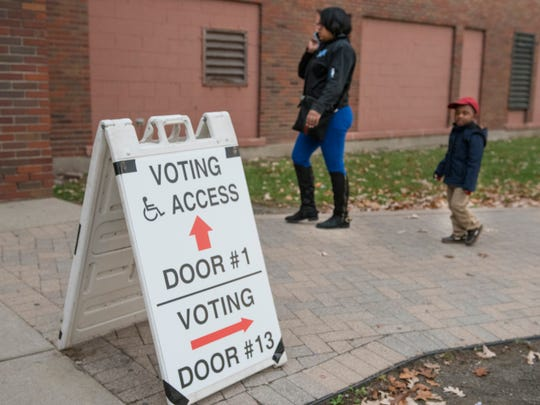 Donita Turner and son Elijah Turner, 3 years old, arrive at the polls at Hilbert Middle School in Redford Twp.