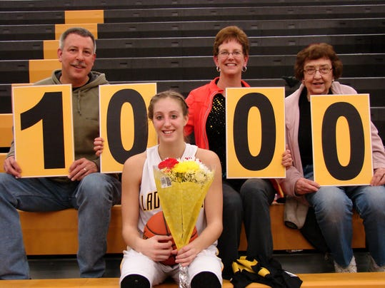 Jenny Horvatinovic poses with, from left, her father, Matt Horvatinovic, mother and grandmother after scoring 1,000 points in a win against New Oxford.
