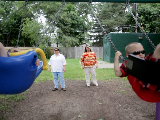 Dana, left, and Diane Shaw, of Rochester Hills, push their adopted sons Charlie, 6, right, and Jacob, 5, on the swings at Geary Park in Ferndale on Friday, June 26, 2015.
