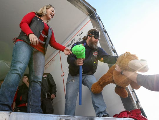 """Bikers """"Tickle"""" and """"Chickle"""" load toy donations  for"""