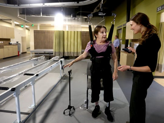 Patricia Burton, left, 69, of Salem, four months after being fitted with a prosthetic leg, uses a harness system to help her balance with the assistance of Lene MacKenzie, a physical therapist, at the Salem Health outpatient rehabilitation center in Salem on Thursday, Feb. 4, 2016. The new center, built on the former property of the Oregon School for the Blind, will start treating patients on Tuesday.