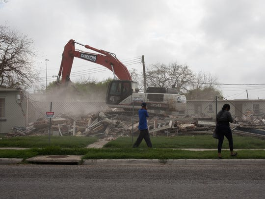 People walk along the fenceline of the D.N. Leathers public housing complex as crews demolish the first of its apartment units Monday. The 75-year-old property will become right-of-way for the new Harbor Bridge.