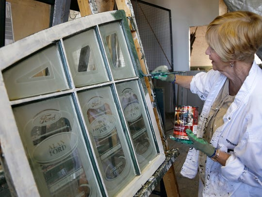 Louise VanderKolk of Canton paints a window at the