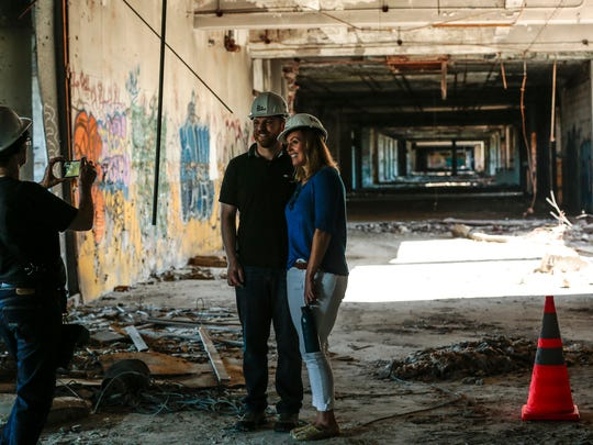 Dawn Dasharion of St. Clair, left, takes a photo of Andrew Cunningham of Royal Oak and Diane LaHaie of Lake Orion in the parking garage during Pure Detroit's Packard Plant tour, Sunday, September 24, 2017 in Detroit.