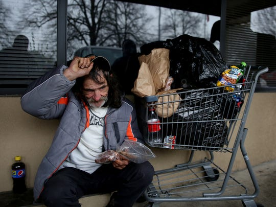 Aaron Adams, 53, eats a sack lunch given to him at