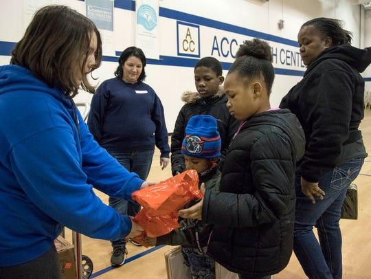 Volunteer Abby Pheonix, 12 of Warren, left, hands gifts