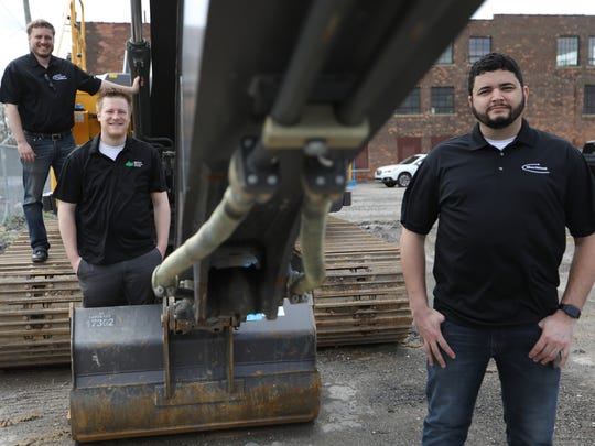 Chief Financial Officer Paul Kaser, from left, Vice President Patrick Beal and Chief Executive Officer Alex Riley of MeritHall with an excavator the company uses for training at the Detroit Training Center on Friday, May 4, 2018.