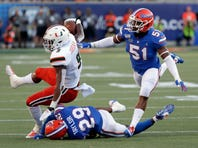 Florida defensive lineman Adam Shuler, left, and defensive lineman Jabari Zuniga celebrate after sacking Miami quarterback Jarren Williams during the first half of an NCAA college football game Saturday, Aug. 24, 2019, in Orlando, Fla. (AP Photo/John Raoux)