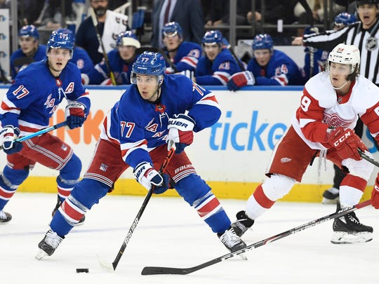 New York Rangers defenseman Tony DeAngelo (77) controls the puck as Detroit Red Wings left wing Tyler Bertuzzi (59) defends during the second period of an NHL hockey game Friday, Jan. 31, 2020, in New York. (AP Photo/Sarah Stier)