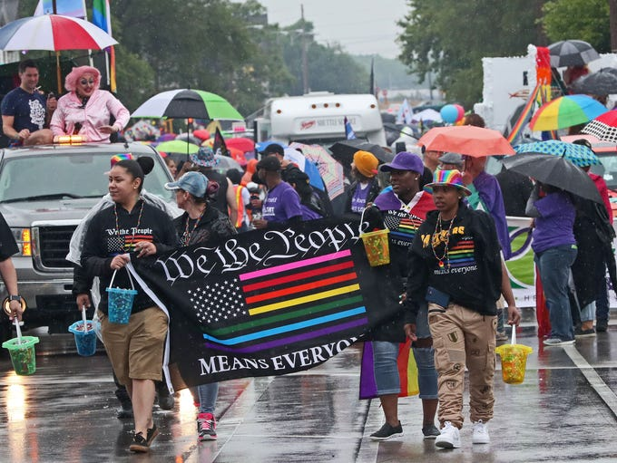 Participants and watchers march in the rain as they