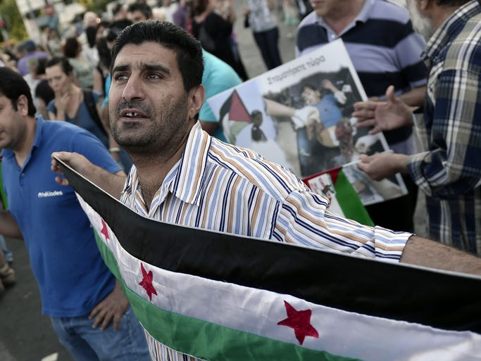 A man holds a Palestinian flag near the Israeli embassy in Athens, Greece, during a demonstration by Palestinians and Greeks who support them. They are  against Israeli air strikes on the Gaza strip.