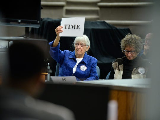 The timekeeper signals a candidate that time has run