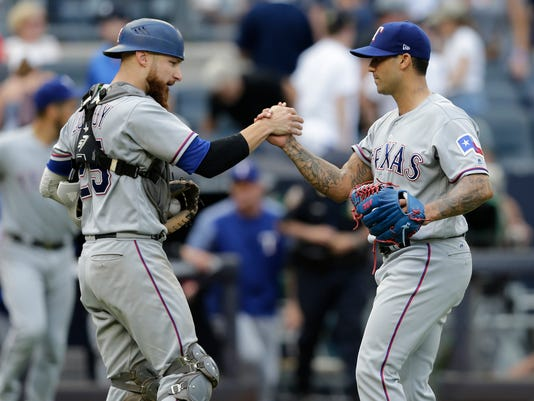 Texas Rangers relief pitcher Matt Bush, right, and catcher Jonathan Lucroy celebrate after the baseball game against the New York Yankees at Yankee Stadium Sunday, June 25, 2017 in New York.  (AP Photo/Seth Wenig)