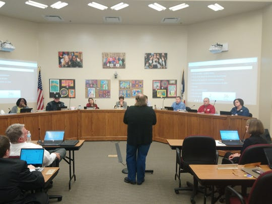 A secretary at an ICCSD board meeting chokes up explaining