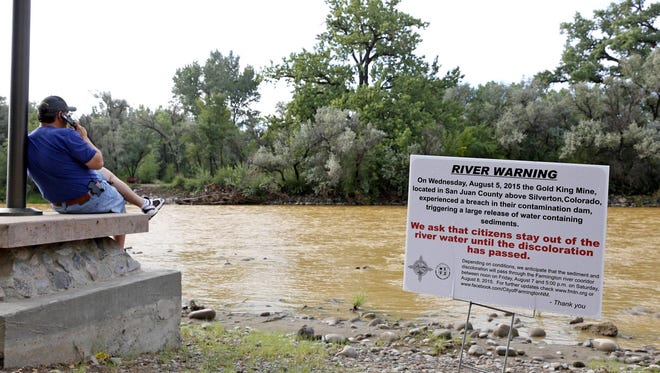 A warning sign from the city is displayed in front of the Animas River as orange sludge from a mine spill upstream flows past Berg Park in Farmington, N.M., on Saturday.