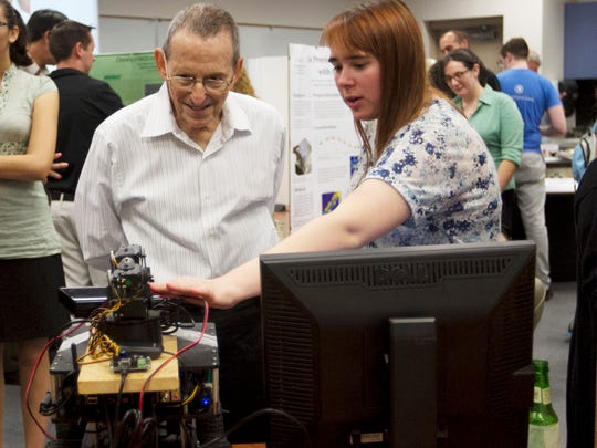 Carly Hessler, right, shows Robert Morantz of Naples her project at the STEM Undergraduate Research Symposium on Friday at FGCU.