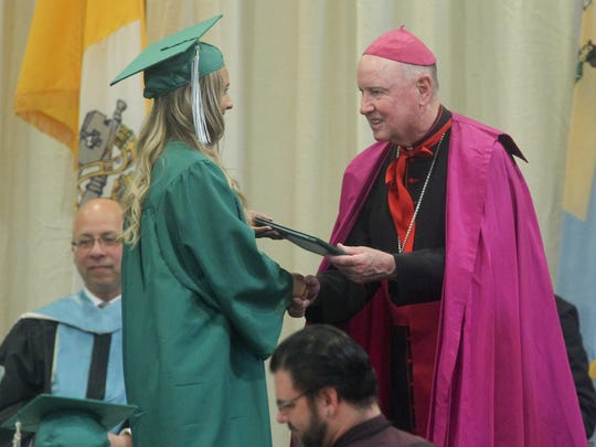 Bishop W. Francis Malooly hands out diplomas during St. Mark's 45th annual commencement exercise Saturday. The school is administered by the diocese.