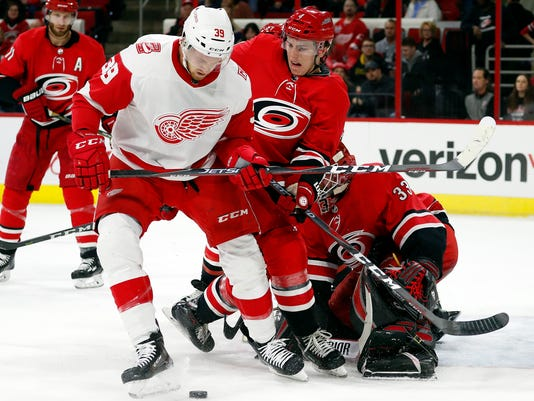 Detroit Red Wings' Anthony Mantha (39) and Carolina Hurricanes' Haydn Fleury (4) work for the puck near the Carolina goal during the first period of an NHL hockey game Friday, Feb. 2, 2018, in Raleigh, N.C. (AP Photo/Karl B DeBlaker)