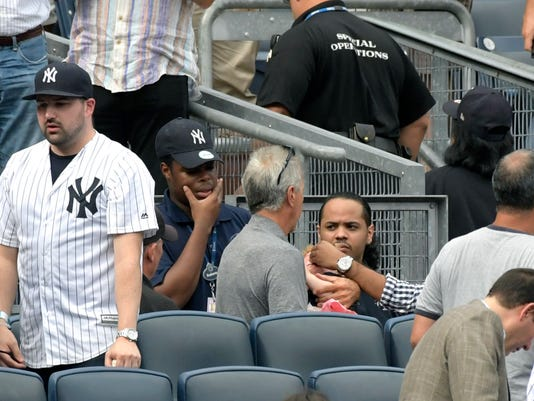 Baseball fans reacts as a young girl is tended to before she is carried out of the seating area after being hit by a line drive in the fifth inning of a baseball game between the New York Yankees and Minnesota Twins, Wednesday, Sept. 20, 2017, at Yankee Stadium in New York. (AP Photo/Bill Kostroun)