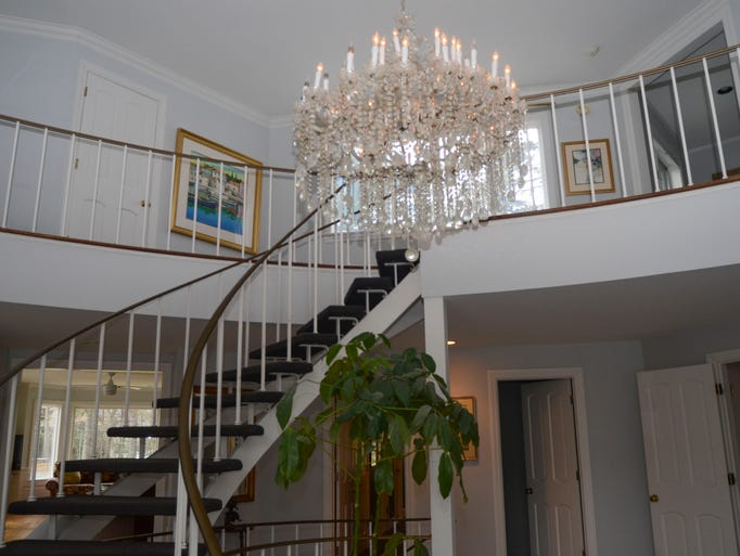 An airy spiral staircase is featured in the entryway