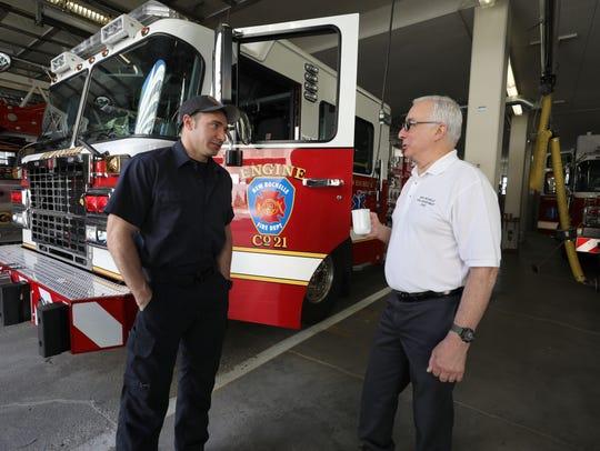 New Rochelle fire chief Louis DiMeglio, right chats
