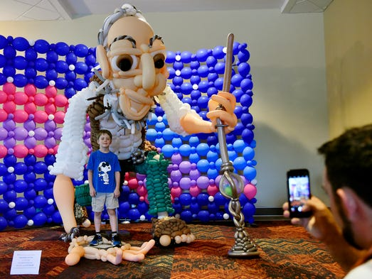 Balloon artist Dustin Queary takes a photo of Sam Wood,