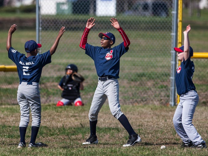 Players warm up before the start of a game between New Castle Little League's minor baseball Indians and Cardinals teams on Opening Day on Saturday afternoon, April 12, 2014.
