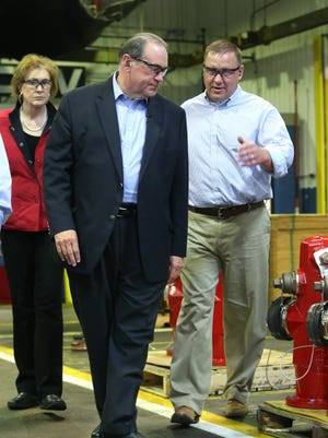 Clow Valve general manager Mark Willett, right, gives Republican presidential hopeful Mike Huckabee a tour of the plant on May 6, in Oskaloosa, Iowa.