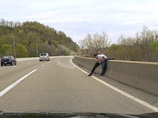 Seen on his dashcam, Riverdale Police Sgt. Greg Bogert grabs a man to prevent him from leaping off an overpass on Route 287. April 25, 2016