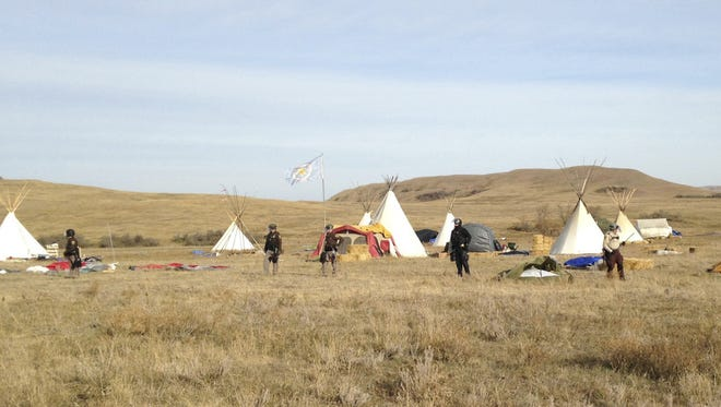 Dakota Access pipeline protester and law enforcement officers who are trying to force them from a camp on private land in the path of pipeline construction stand off, Thursday, Oct. 27, 2016 near Cannon Ball, N.D. Soldiers and law enforcement officers dressed in riot gear began arresting protesters who had set up a camp on private land to block construction of the Dakota Access oil pipeline.