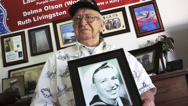 In this Thursday, Nov. 17 photo, Lauren Bruner, one of five remaining survivors of the USS Arizona which was attacked on Dec. 7, 1941, holds with a 1940 photo of himself, at his home in La Mirada, Calif. Bruner was getting ready for church when the alarm on his battleship sounded.