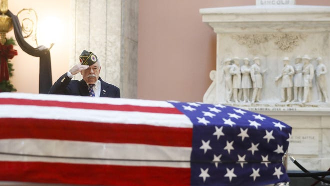 Warren Motts salutes the casket of the John Glenn as Glenn lies in repose, Friday, Dec. 16, 2016, in Columbus, Ohio.
